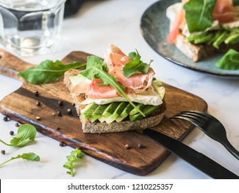 Toasts with camembert cheese, avocado slices, prosciutto, arugula and spices on wood board on marble table
