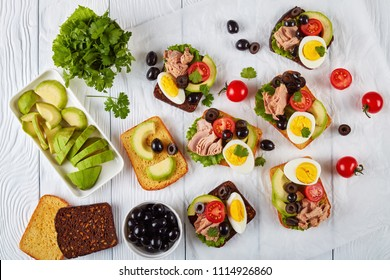 toasts with canned tuna, avocado slices, lettuce, tomatoes, black olives and hard boiled egg on rye and corn toasted bread slices on a paper, view from above, flat lay