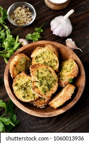 Toasts with cheese, greens and garlic in bowl on wooden table, top view