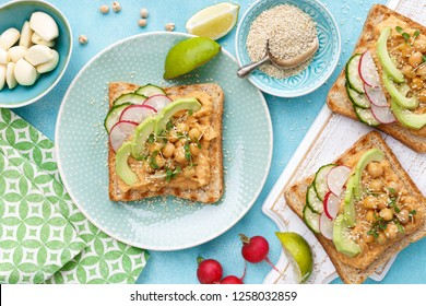 Toasts with chickpea hummus, avocado, fresh radish, cucumber, sesame seeds and flaxseed sprouts. Diet breakfast. Delicious and healthy plant-based vegetarian, vegan food. Flat lay. Top view