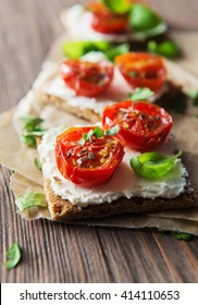 Toasts (Crostini) with ricotta and cherry tomatoes on wooden background