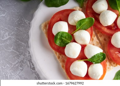 toasts with mozzarella, tomatoes and spinach in a white plate