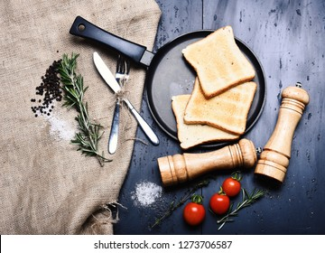 Toasts on frying pan on grey background near sackcloth, saltcellar and pepperbox. Slices of roast bread with tomatoes, thyme, fork and knife. Breakfast at home, restaurant. American tradition concept