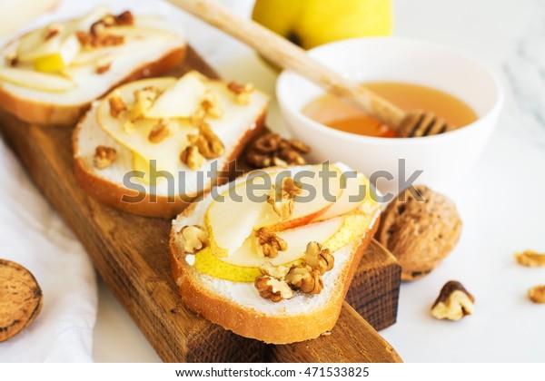 Toasts avec poire, fromage à la crème, noix et miel. Mise au point sélective