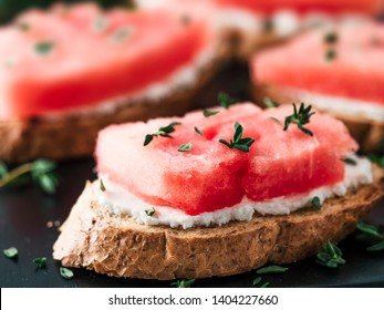 Toasts with soft cheese, watermelon and fresh thyme.Salty cheese,sweet watermelon and spicy thyme on crispy grilled bread slices. Idea and recipe for unusual healthy breakfast, summer snack or lunch