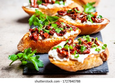 Toasts with sun-dried tomatoes and cream cheese on a black board, dark background.