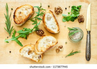 Toasty bread, jar with paste, herbs and wallnuts on a wooden board.
