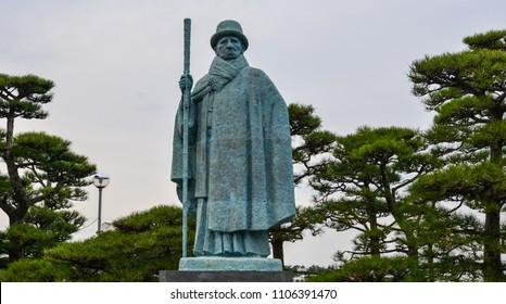 Toba, Japan - Mar 18, 2018. Statue of Mikimoto Kokichi with pine tree garden on Pearl Island in Toba, Japan.
