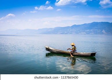 Toba lake in North Sumatra, Indonesia - March 18 2015: The seller of fruit floats on a wooden boat on a volcanic Toba lake. Wanderlust travel concept.