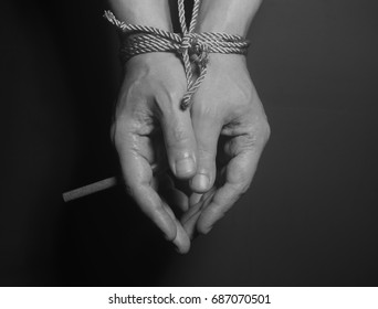 Tobacco addiction. Cigarette on male hands tied with a rope.