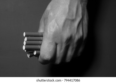 Tobacco addiction. Cigarettes on man hand on black background.