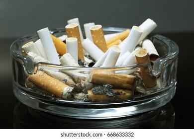 Tobacco cigarettes ashtray on background black.