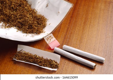 Tobacco and hand rolled cigarettes on table