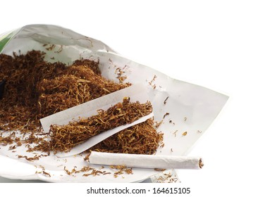 Tobacco and rolled cigarettes on white background