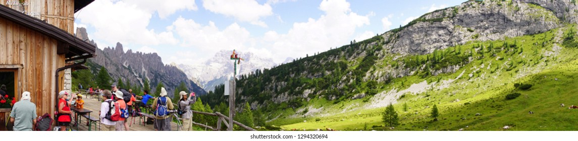 TOBLACH, ITALY - AUG 3, 2018 - Hikers take a break for lunch and picture taking in the Dolomite Alps near Toblach, Italy