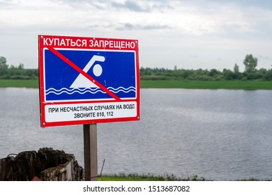 Tobolsk, Russia, 07/27/19: Information sign on the background of the pond, the text in Russian-swimming is prohibited.