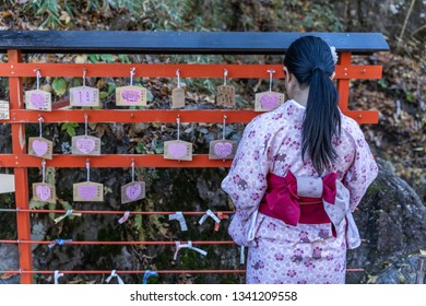 TOCHIGI, JAPAN - NOVEMBER 15, 2018: woman staning in front of Wooden prayers at Nikko, Tochigi Prefecture, Japan