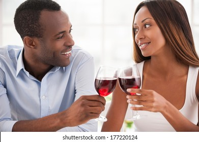 Today is their special date. Beautiful young African couple sitting close to each other and holding wineglasses