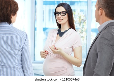 Today women working during pregnancy - happy pregnant woman talking with colleagues in modern business office.