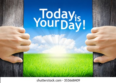 """Today is your day! Hand opening an old wooden door and found wording """"Today is your day!"""" over green field and bright blue Sky Sunrise."""