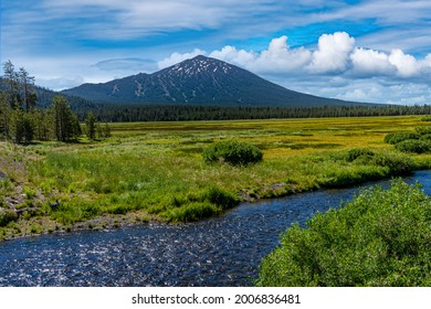 Todd creek and Mt Bachelor mountain with white puffy clouds in the late afternoon on a hot summer day, on Century Drive near Bend Oregon