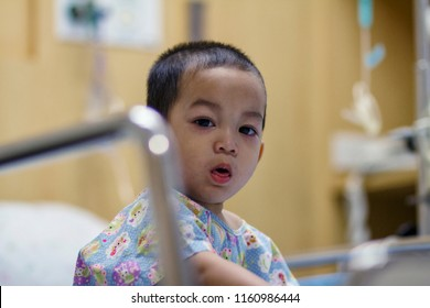 Toddler Asian boy sick and suffering from a cough and running nose and hi fever.Boy rest in patient bed in hospital. And in patient suit.