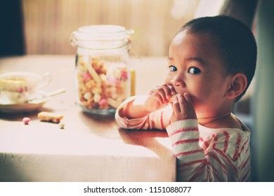 Toddler Asian boy with skinhead hair style eating Chinese sweetmeat or snack.Vintage color tone.
