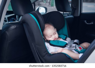 The toddler Asian boy is sleeping at his car seat.Focus on face