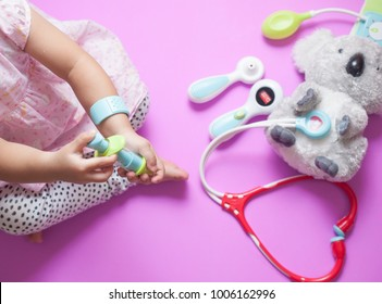 Toddler asian girl hold syringe while playing as doctor