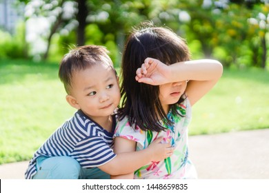 Toddler baby boy hug and encourage big sister when she fall down in the playground park.Toddler kid help his sibling.Family with children at home.Love, trust and tenderness.