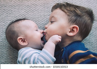 Toddler baby boy kisses his happy brother