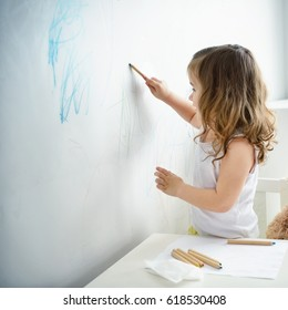 Toddler baby girl  coloring a wall