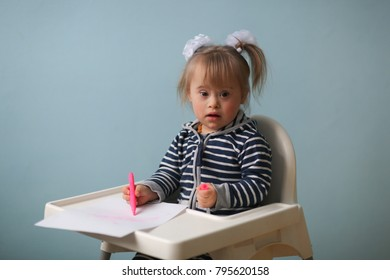 Toddler baby girl with Down syndrome draws in a children's chair, creativity and rehabilitation, lifestyle and toning