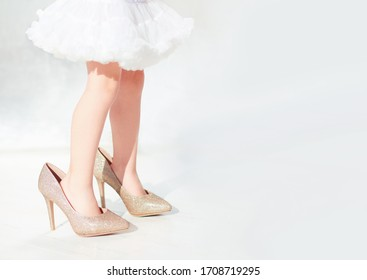 toddler baby girl is trying the shiny high heel shoes on
