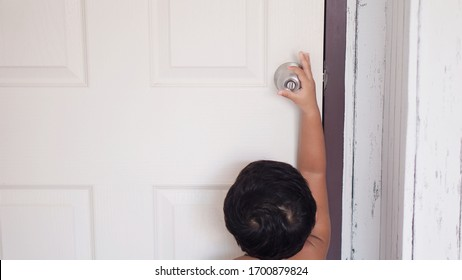 toddler baby hands Kid reaching up try to open or close door knob, Child want to escape to play, explore outdoor, Security and Safety Concept.