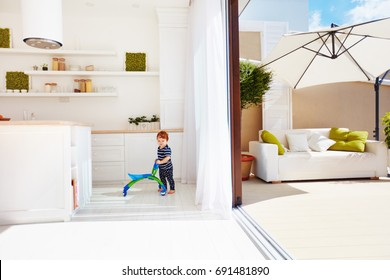 a toddler baby walking with go-cart on open space kitchen and rooftop patio with sliding doors