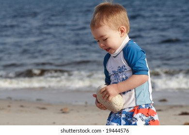 Toddler at the Beach moving a rock