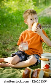 Toddler beautiful boy drinking milk and eating a sweet bun on a green grass