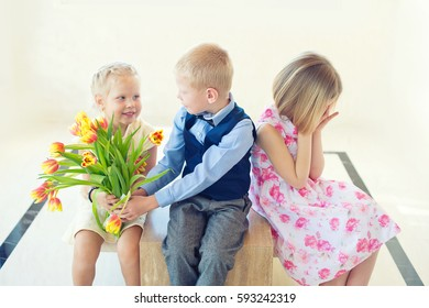 Toddler blond boy gives a bouquet of tulip flowers to one little girl as a present on spring holiday or birthday. Another child is upset and cry.