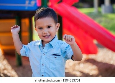 A toddler boy with arms raised up and a smile on his face, playing in a colorful kids playground.