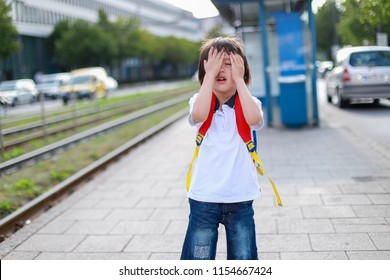 Toddler boy with backpack covered his face with hands at tram stop look like he missed some train or sad. back to school concept