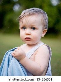 Toddler boy with blue eyes in overalls outside in grass holding on to blue blanket looking nervous