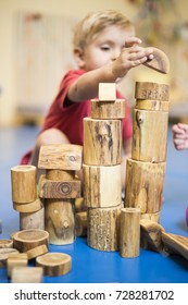 toddler boy building with natural wood blocks in kindergarten