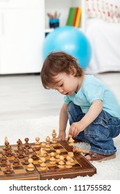 Toddler boy crouching and playing with chess pieces