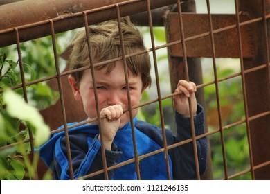 toddler boy crying behind bars