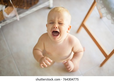 A toddler boy crying on the room's floor