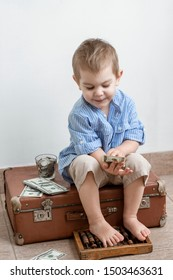 Toddler boy with dollars sitting on an old suitcase.  Financial support, business, family, alimony, maintenance, investing in children .Learning financial responsibility and planning savings concept.