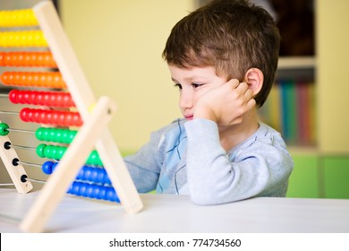 Toddler boy feeling bored and tired while playing with abacus at kindergarten. Hyperactive kid having concentration deficit disorder