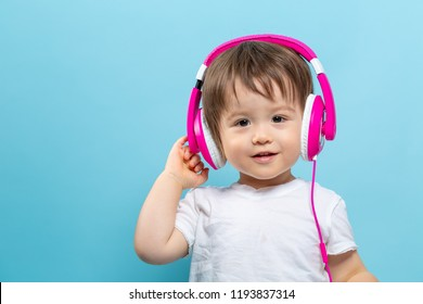 Toddler boy with headphones on a blue background