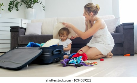 Toddler boy helping his mother packing thing for summer beach vacation